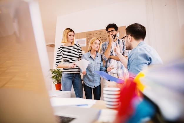 Взволнованная и раздраженная женщина, разговаривающая со своим расстроенным боссом, в то время как коллеги стоят рядом с ней в офисе