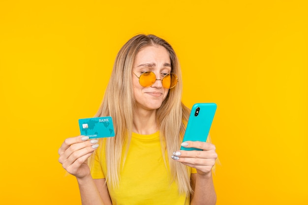 걱정스럽고 어색한 귀여운 소녀가 실수를 저질렀 고, 실수로 쇼핑 중에 남자 친구의 돈을 모두 낭비하고 신용 카드를 들고있었습니다. 온라인 쇼핑 개념.