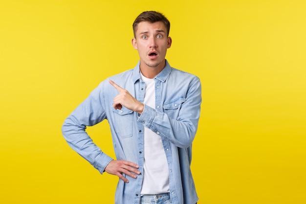 Обеспокоенный и обеспокоенный белокурый красивый парень, выглядящий неуверенно и встревоженно, указывая пальцем в верхнем левом углу, встревоженно смотрит в камеру, чувствуя себя напуганным, стоя на желтом фоне.