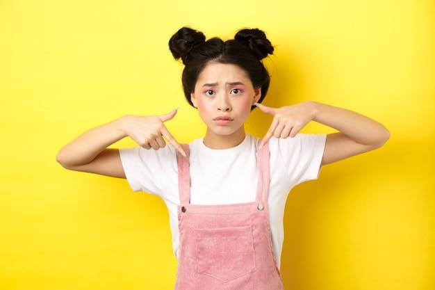 グラマーメイクで心配して混乱しているアジアの女の子、指を下に向けて悲しそうに見え、ピンクに対して夏服で立っています。