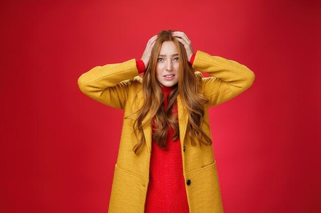 頭に手をつないで心配してびっくりした赤毛の女の子は、問題を抱えて歯を食いしばって心配し、心配して眉をひそめ、プロジェクトが赤い背景をフェイルオーバーすることに神経質になりました。