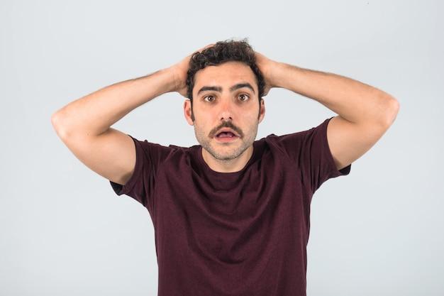 彼の頭に手で口ひげを生やして心配し、圧倒された若い男。紫のtシャツと孤立した白い背景。