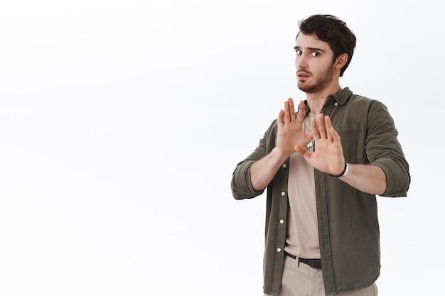 싸움을 피하는 걱정되고 겁 먹은 잘생긴 청년. 남자는 뒤로 물러서서 손을 들어 중지, 거부 또는 방어적인 제스처를 취합니다.