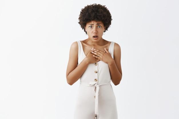 Обеспокоенная и обеспокоенная стильная девушка позирует у белой стены