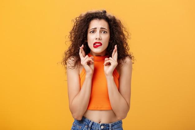 Sciocco femmina caucasica preoccupata e ansiosa con i capelli ricci in rossetto rosso e la parte superiore tagliata che morde il labbro inferiore nervosamente guardando le dita incrociate preoccupate per buona fortuna che esprimono desideri sul muro arancione.