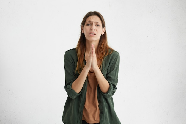 Worried apologetic brunette woman having some difficulties pressing her palms together begging for apologize. apprehensive female expressing her anxiety asking god for health isolated over white wall