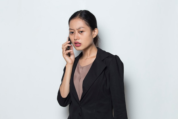 Worried asian business woman with mobile phone