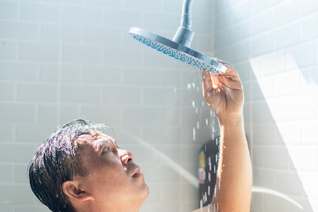 Worried asian man takes a shower