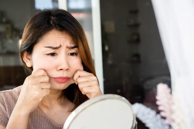 걱정 아시아 여자 손 뺨에 그녀의 뚱뚱한 피부를 당기고 거울, 노화 및 과체중 개념에 그녀의 얼굴을 확인