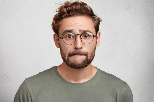 Worried bearded guy in eyewear, bites lower lip, anticipate important decision or feels nervous