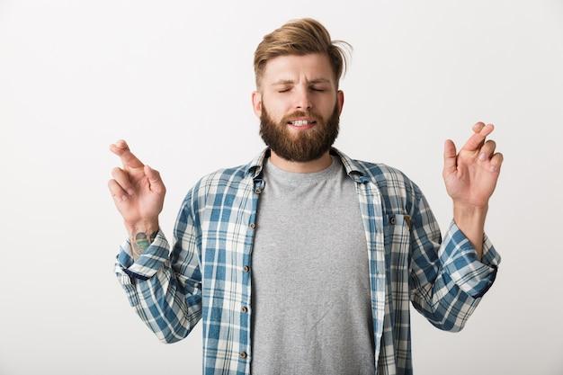 Обеспокоенный бородатый мужчина, одетый в клетчатую рубашку, стоит изолированно, скрестив пальцы на удачу