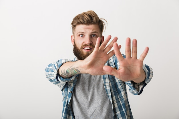 Worried bearded man dressed in plaid shirt standing isolated, otstretched hands