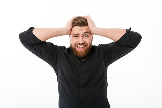 Worried bearded man in shirt holding his head