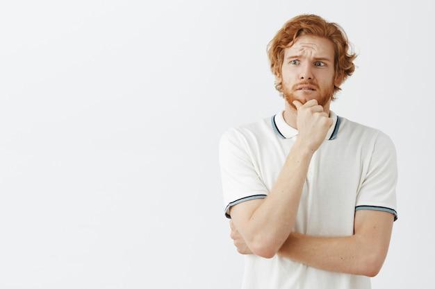 白い壁にポーズをとって心配しているひげを生やした赤毛の男