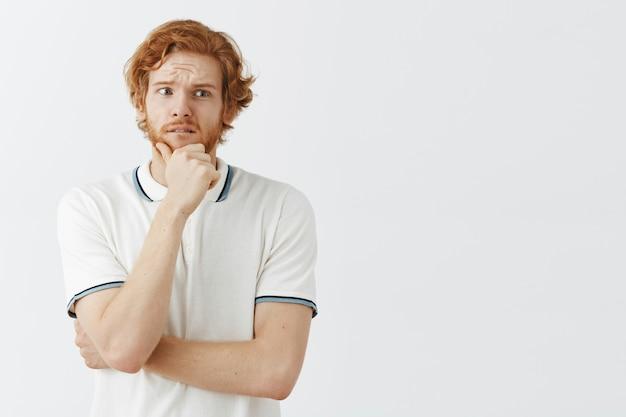 Ragazzo dai capelli rossi barbuto preoccupato in posa contro il muro bianco