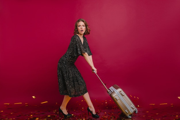 Bella ragazza preoccupata in abito lungo vintage trascinando grande valigia