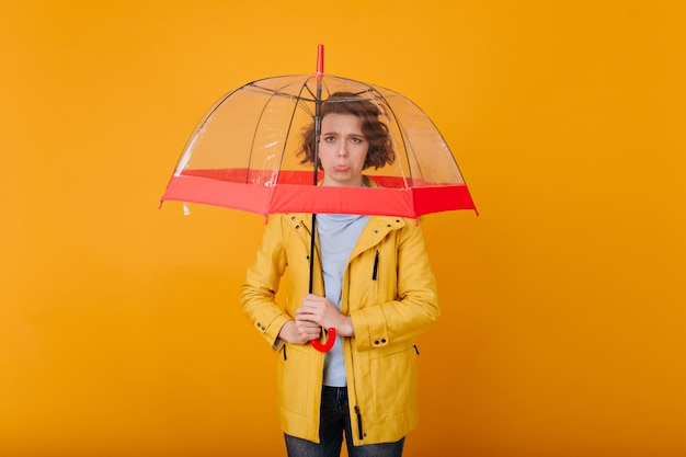 Worried beautiful girl with short hair standing under umbrella.  portrait of upset caucasian woman in raincoat holding stylish parasol.