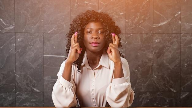 Обеспокоенная черная дама в блузке держит скрещенные пальцы дрожащих рук и улыбается от счастья, сидя за офисным столом у серой мраморной стены, солнечный свет