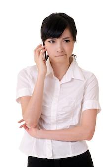 핸드폰을 들고 흰색 배경에서 듣고 걱정 된 비즈니스 여자.