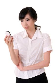 핸드폰을 들고 흰색 배경에 찾고 걱정 된 비즈니스 여자.