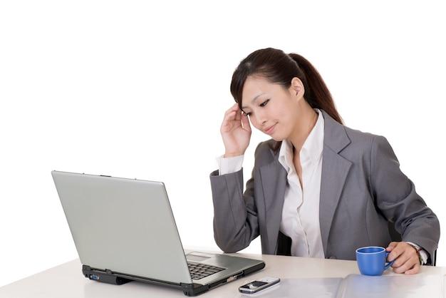 白い背景の机の上でラップトップで作業している心配のビジネス女性。