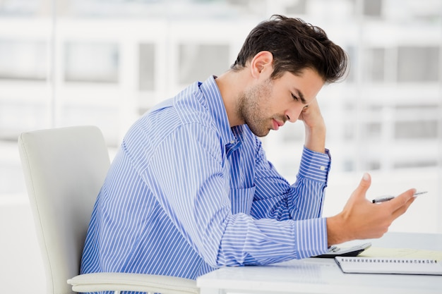 Worried businessman calculating accounts on a calculator