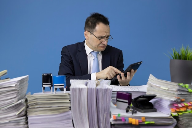 Worried businessman counts on calculator sitting at table with piles of papers in office