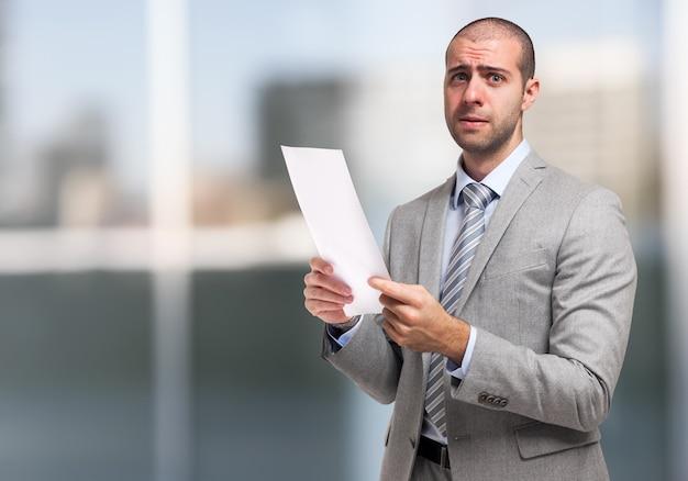 Обеспокоенный бизнесмен, держащий документ