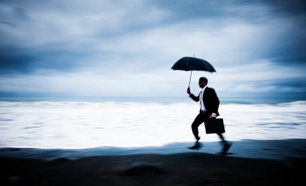 Worried businessman running by the beach