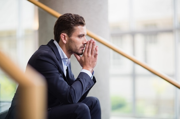 Worried businessman sitting on steps