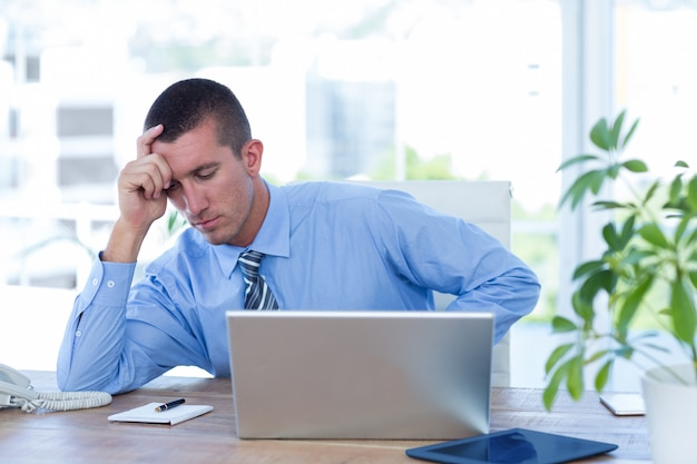 Worried businessman with head in one hand