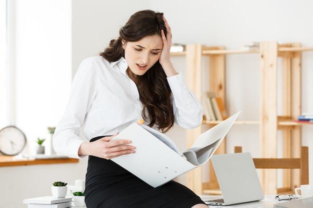 Обеспокоенная деловая женщина, читая отчет об уведомлении, работая, сидя за столом в офисе.