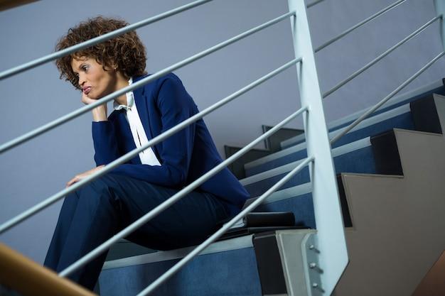 会議センターの階段に座っている心配している実業家
