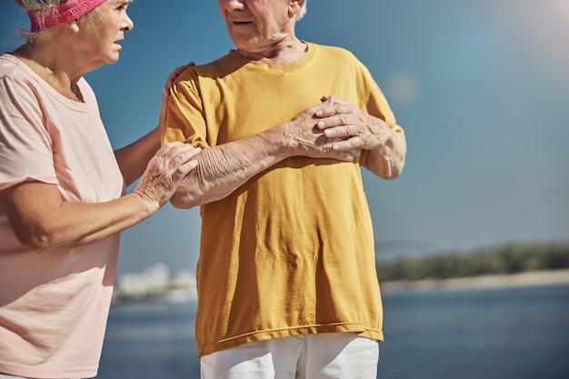 심장 부위의 통증을 겪고있는 회색 머리 남편을보고 걱정되는 백인 노인 여성