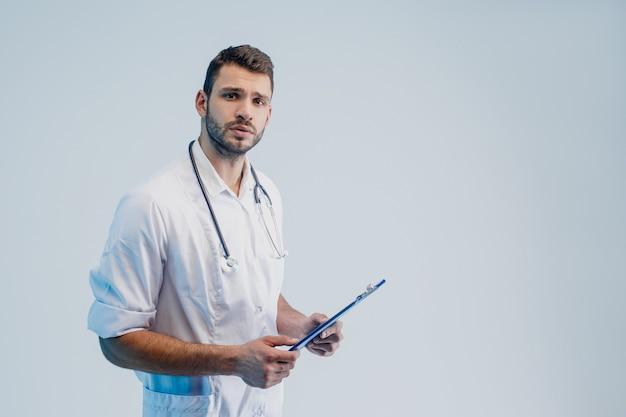 Взволнованный кавказский мужчина-врач со стетоскопом и доской сзажимом для бумаги. молодой бородатый мужчина в белом халате. изолированные на сером фоне с бирюзовым светом. студийная съемка. скопируйте пространство.