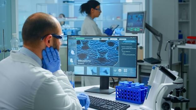 과학 현대 장비를 갖춘 실험실에서 백신 진화를 검사하는 pc에서 작업하는 걱정 된 화학자 의사