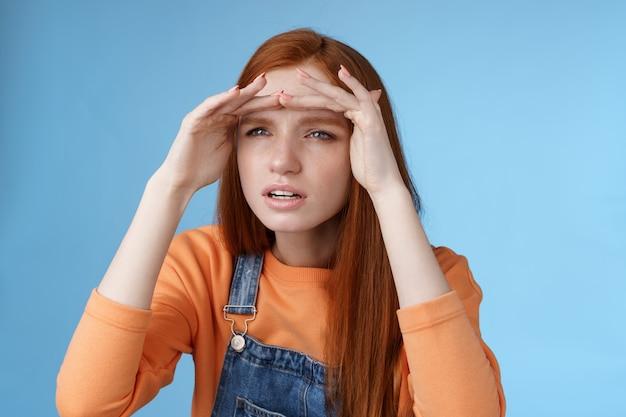 걱정되는 집착 빨간 머리 여자 친구가 거리에서 남자 친구 피어를 훔쳐 보는 초점 시력 멀리서 손을 잡고 이마 커버 눈 햇빛 서 집중 파란색 배경