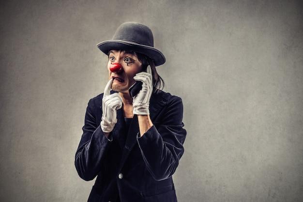 Взволнованный клоун разговаривает по телефону