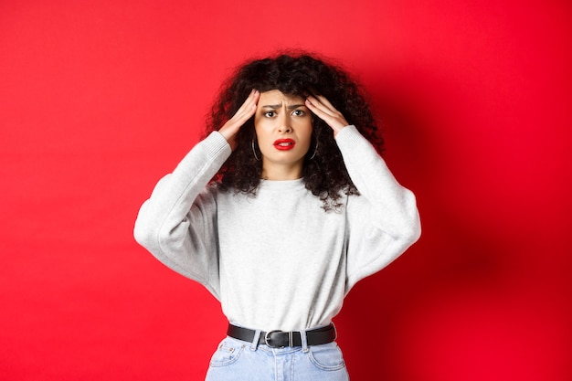 Worried and concerned young woman touching head and grimacing, having headache, standing with migraine on red wall