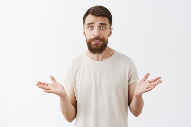 Uomo barbuto preoccupato e confuso che posa contro il muro bianco