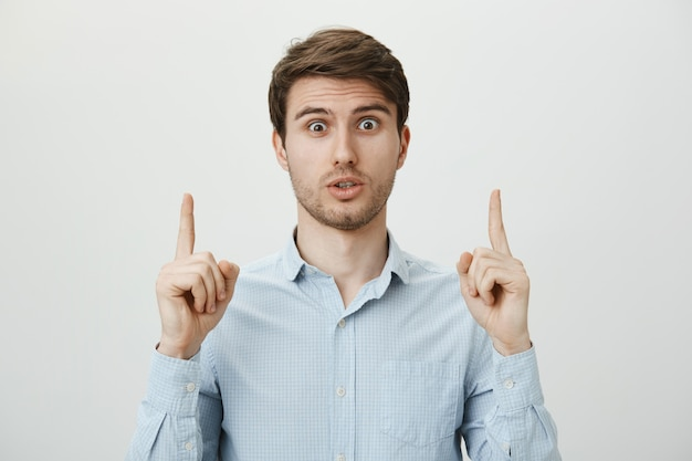 Worried confused guy pointing fingers up, asking question about promo