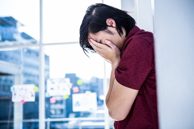 Worried creative businessman leaning on wall in office