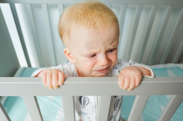 Worried cute baby standing in crib, holding railing, crying and looking away. closeup shot, high angle. child care or childhood concept