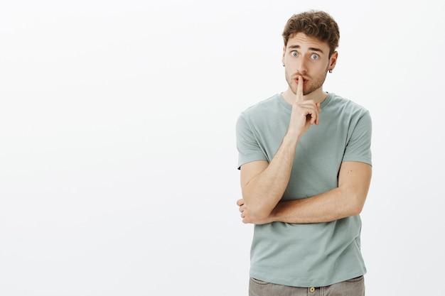 Обеспокоенный милый европейский парень со светлыми волосами в серьгах, говоря шшш и умоляющий сохранить секрет в секрете, показывает жест шиша с указательным пальцем над ртом