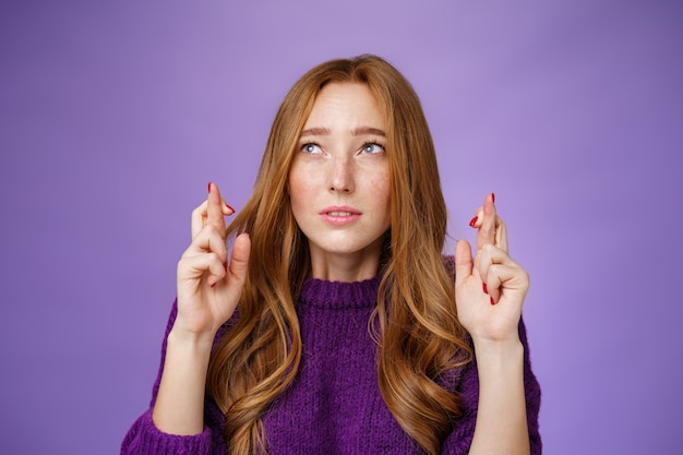 Worried cute female redhead student with freckles squinting and focusing on making wish as crossing fingers for good luck looking at upper left corner with faith and anticipation over purple wall.