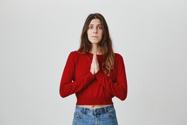 Worried cute girl begging help, asking advice with hands in pray gesture