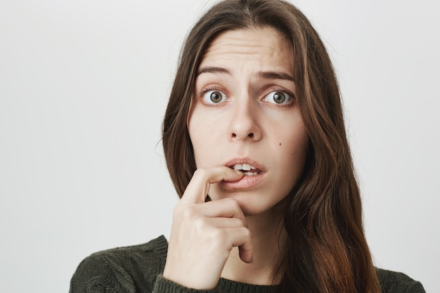 Worried cute woman biting finger, look indecisive