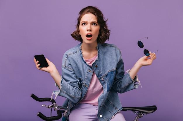 電話でポーズをとって心配している暗い目の女性。自転車の横に立っているデニムジャケットの感情的な白人女性の屋内写真。
