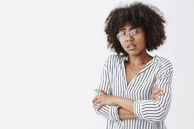 Worried dark-skinned female model with curly hair in glasses and office striped blouse holding hands on chest frowning form empathy and anxiety over gray wall