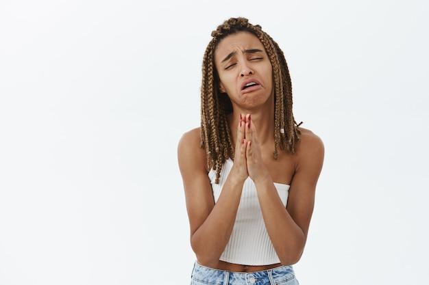 Обеспокоенная темнокожая девушка умоляет о помощи, дуется и в отчаянии умоляет